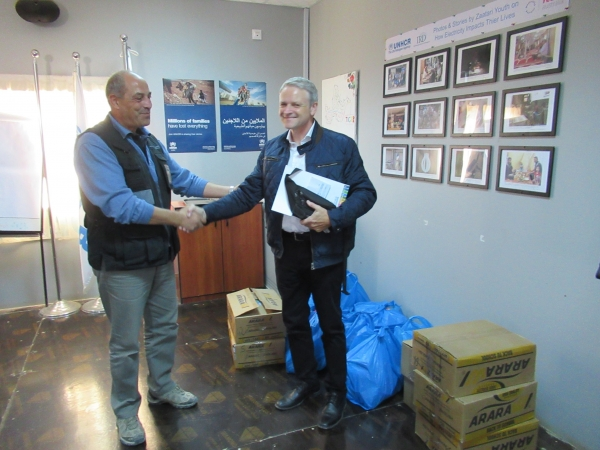 Photograph of Mohammed Al Taher, UNHCR Liaison Officer accepting the gifts (notebooks, pens, pencils etc) from Colonel Urs Amiet, GCSP.
